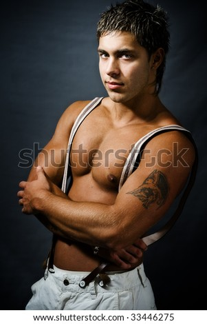 Handsome muscular young man with arms folded - stock photo