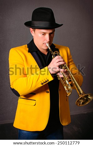 Handsome musician trumpet player playing trumpet at studio. Jazz-band - stock photo