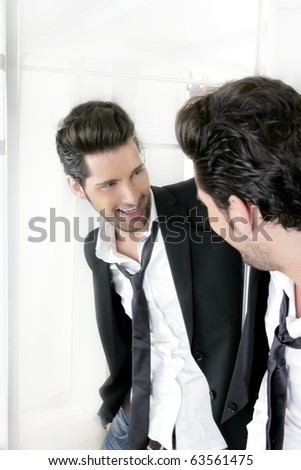 Handsome narcissistic suit proud young man looking himself in the mirror - stock photo