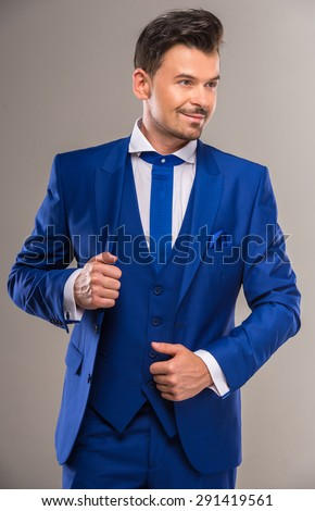 Handsome nifty man in stylish blue suit and tie posing at studio. - stock photo