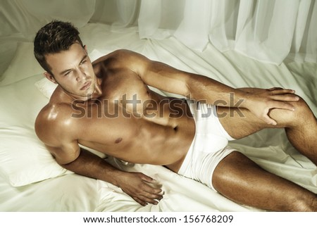 Handsome nude man lying in a bed. - stock photo