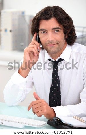 Handsome office worker making a phone call - stock photo