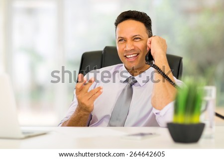 handsome office worker talking on telephone - stock photo