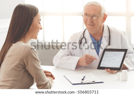 Handsome old doctor in white medical coat and eyeglasses is showing test results on tablet to his patient. Both are smiling while sitting in his office