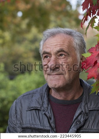 handsome old italian man in a park at fall - stock photo