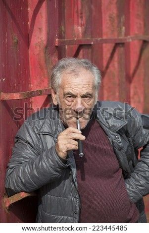 handsome old italian man smoking an electronic cigarette - stock photo