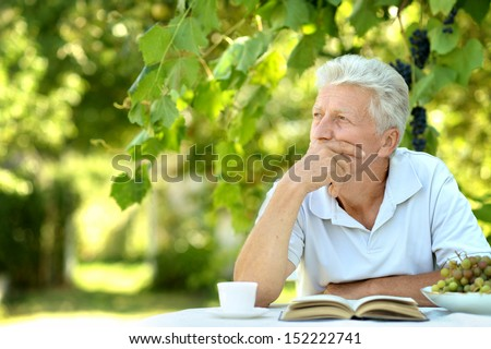 Handsome older man sitting at a table at home on the veranda - stock photo