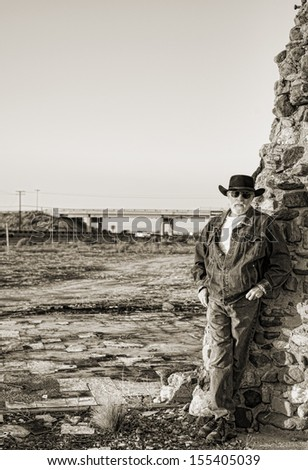 handsome older man with a gray beard wearing a black cowboy hat leaning against an old stone chimney with a freeway and overpass in the background - stock photo