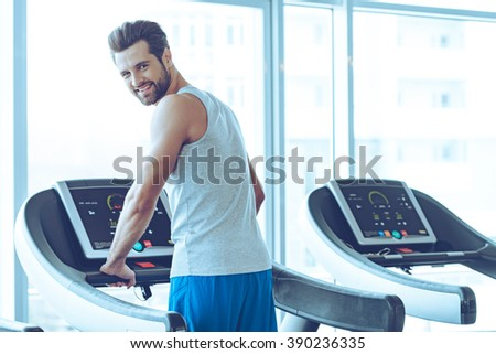 Handsome on treadmill. Rear view of young handsome man in sportswear standing on treadmill in front of window at gym and looking at camera with smile - stock photo