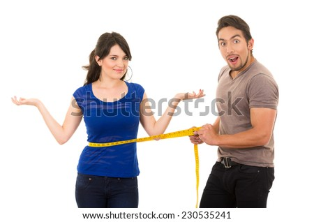 handsome open mouthed man holding measuring tape around thin fit young girl's stomach concept of dieting fitness weightloss  isolated on white - stock photo