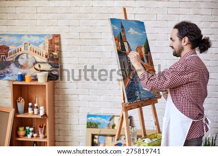Handsome painter working in his studio - stock photo