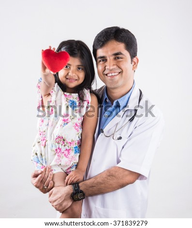 handsome pediatric doctor holding a baby girl, male doctor with small girl, indian doctor, indian girl patient with red heart stuffed toy, heart care concept and doctor with girl patient, isolated  - stock photo