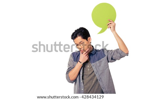 Handsome pensive young Chinese man is holding speech bubble, looking down and thinking, isolated on white background - stock photo