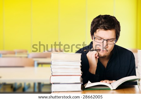 Handsome pensive young man studying on a stack of books on desk at school - stock photo