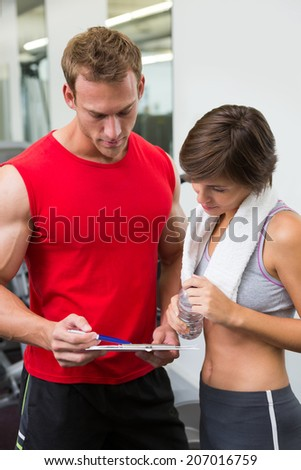 Handsome personal trainer with his client looking at clipboard at the gym - stock photo