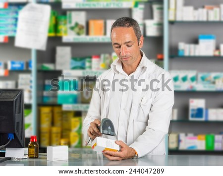 Handsome Pharmacist at Work in a Drugstore - stock photo