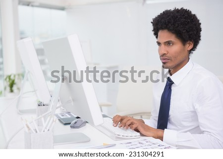 Handsome photo editor working at desk in his office - stock photo