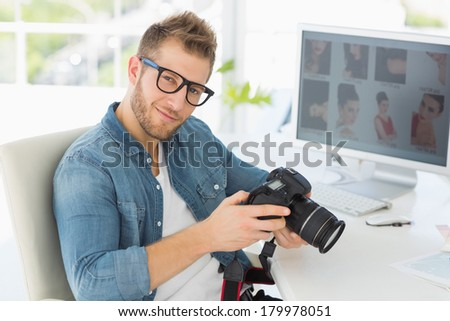 Handsome photographer holding his camera smiling at camera in creative office - stock photo