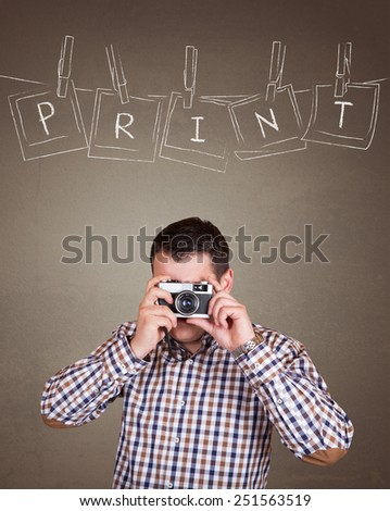 Handsome photographer man taking a picture with old retro (vintage) camera on old brown wall background with  photo frames hanging on a rope held by clothespins design concept  - Print text - stock photo