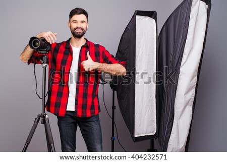 """Handsome photographer with camera in photo studio gesturing """"LIKE"""" - stock photo"""