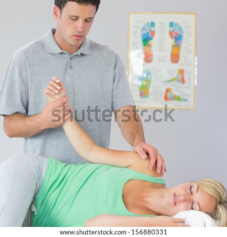 Handsome physiotherapist treating patients arm in bright office - stock photo