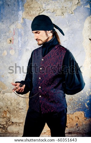 Handsome pirate holding pocket watch - stock photo