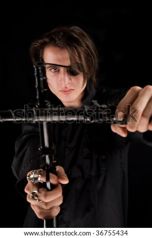 Handsome pirate with eye-patch and scary eye crossing the guns, Halloween theme - stock photo