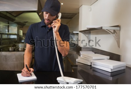 Handsome pizza delivery man taking an order over the phone in a commercial kitchen - stock photo