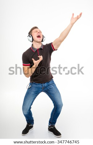 Handsome playful young male in black t-shirt and jeans listening to music using headphones, singing and dancing over white background - stock photo