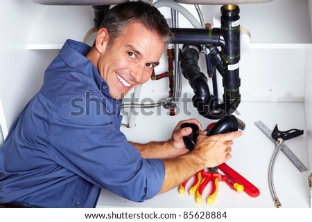 Handsome plumber doing sink repararion in kitchen.