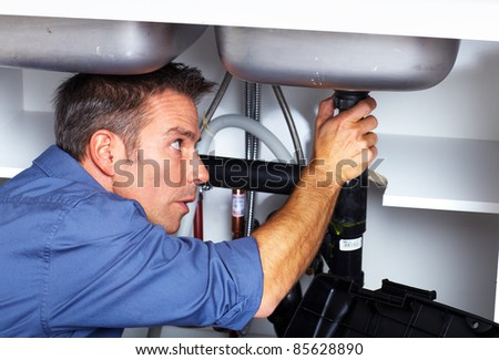 Handsome plumber doing sink repararion in kitchen. - stock photo