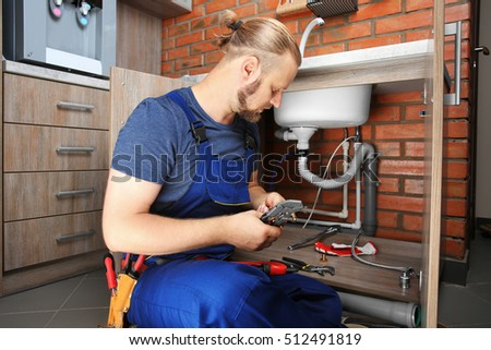 Handsome plumber repairing sink pipes in kitchen