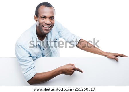 Handsome pointing copy space. Cheerful African man in blue shirt leaning at copy space and pointing it while standing against white background - stock photo