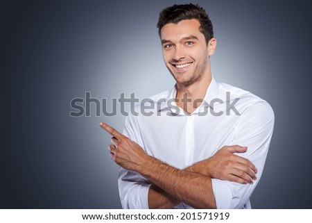 Handsome pointing copy space. Happy young man in white shirt looking at camera and smiling while standing against grey background and pointing copy space - stock photo