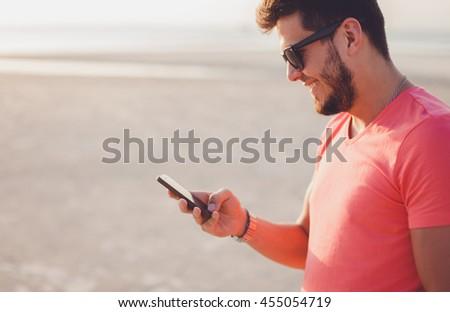 handsome portrait mam using smartphone, happy face, sunglasses, beard, beach, sea, travel, internet - stock photo