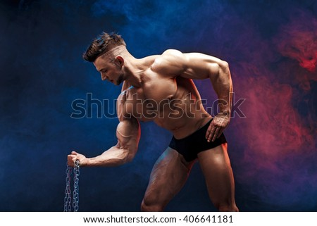 handsome power athletic man bodybuilder doing exercises with chain. Fitness muscular body on dark smoky background. Perfect male. Awesome bodybuilder, posing.  - stock photo