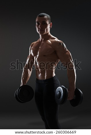 Handsome power athletic man bodybuilder doing exercises with dumbbell, confidently looking forward. Fitness muscular body on dark background with clipping path - stock photo
