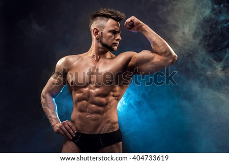 Handsome power athletic man bodybuilder. Wet Fitness muscular body on dark smoke background. Perfect male. Awesome bodybuilder, posing.  - stock photo