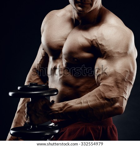 Handsome power athletic man in training pumping up muscles with dumbbell. Strong bodybuilder with six pack, perfect abs, shoulders, biceps, triceps and chest. - stock photo