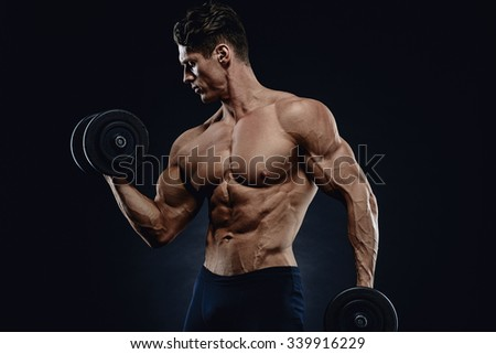 Handsome power athletic man in training pumping up muscles with dumbbell. Strong bodybuilder with six pack, perfect abs, shoulders, biceps, triceps and chest.
