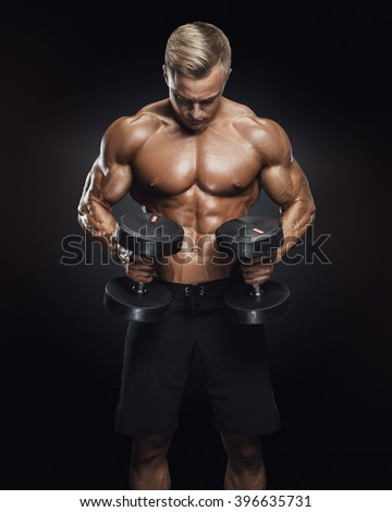 Handsome power athletic man in training pumping up muscles with dumbbells in a gym. Fitness muscular body isolated on dark background. - stock photo