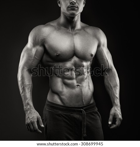 Handsome power athletic man posing on black background. Strong bodybuilder with six pack, perfect abs, shoulders, biceps, triceps and chest - stock photo