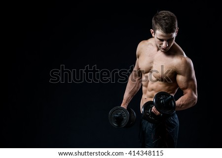 Handsome power athletic man training pumping up muscles with dumbbells in a gym. Fitness muscular body isolated on black background. Looking to his biceps. - stock photo