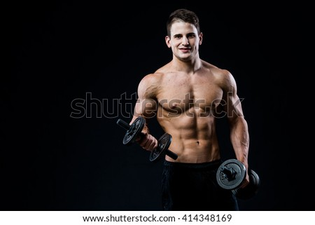 Handsome power athletic man training pumping up muscles with dumbbells in a gym. Fitness muscular body isolated on black background. Looking to the camera.