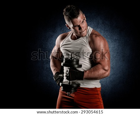 Handsome power athletic man with dumbbell confidently looking forward