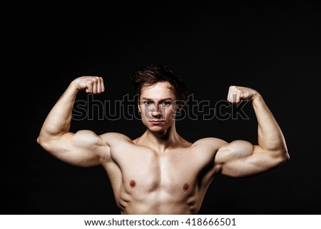 Handsome power athletic man with dumbbell confidently looking forward. Strong bodybuilder with six pack, perfect abs, shoulders, biceps, triceps and chest. Great fitness body. Ideal for commercial  - stock photo