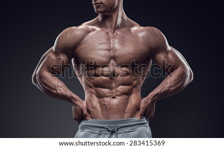 Handsome power athletic young man with great physique. Strong bodybuilder with six pack, perfect abs, shoulders, biceps, triceps and chest. Image have clipping path - stock photo