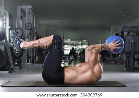 Handsome powerful athletic man performing abs exercise with medicine ball. Strong bodybuilder with perfect abs and arms.