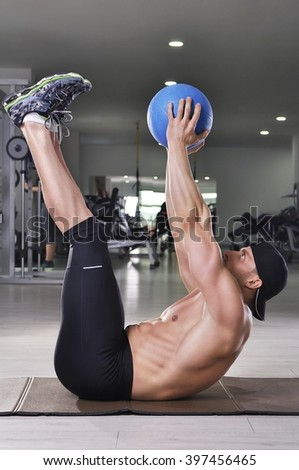 Handsome powerful athletic man performing crunches with medicine ball. Strong bodybuilder with perfect abs, arms and back. - stock photo
