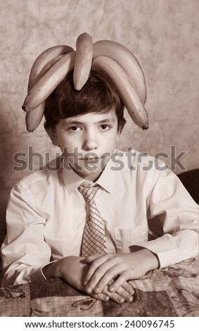 handsome preteen boy expressive portrait with banana on head - stock photo